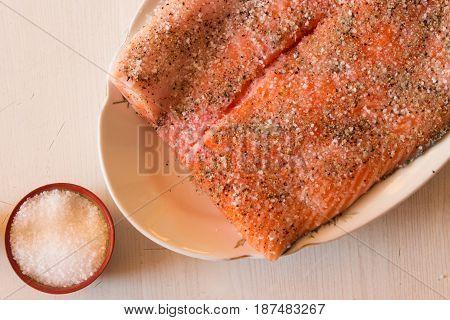 Salting raw salmon fish with lemon pepper sea salt. Top view.