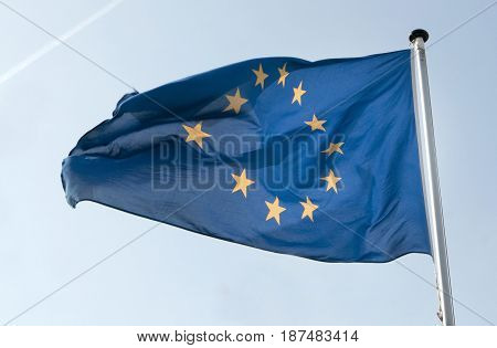 The flag of the European Union as it waves in the wind. Its dark blue colour is in beautiful contrast to the light blue sky.
