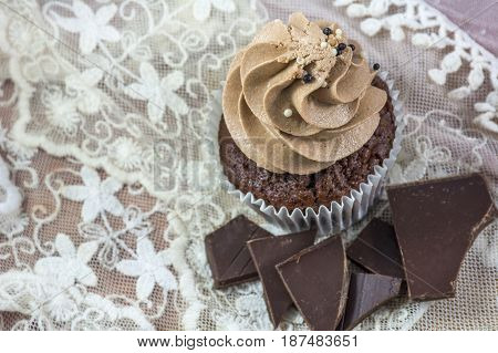 Brown cupcake with cream and chocolate on the pink lace background