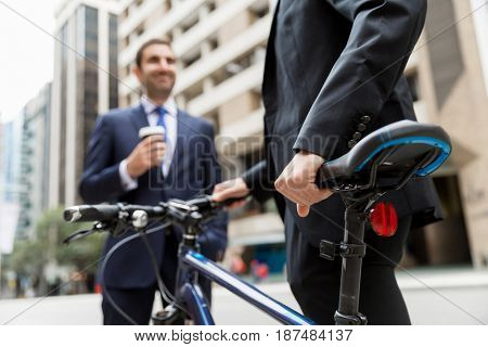 Two young businessmen with a bike in city centre