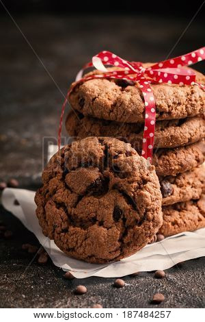 Stack of freshly baked chocolate chip cookies on rustic background