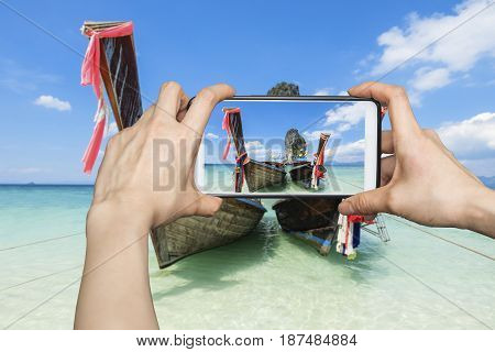 Tourist taking a photo of long tail on beautiful Po-Da Isalnd in Krabi, Thailand with smartphone