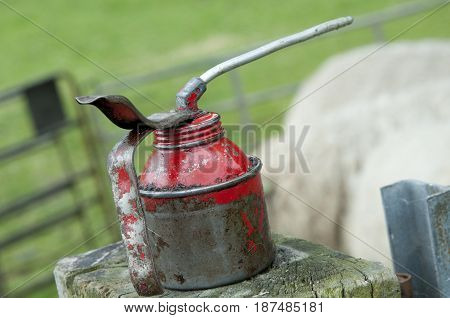 A worn out red gas tank standing on a piece of wood.