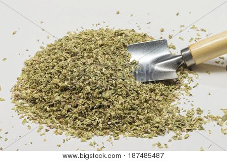 A pile of dried oregano leaves and a shovel