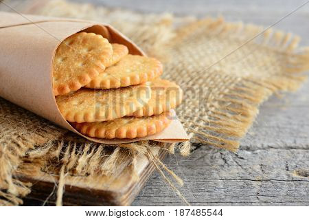 Salty thin crackers in a wrapping paper and on a sackcloth. Vintage wooden background. Tasty crispy crackers snack idea for children and adults
