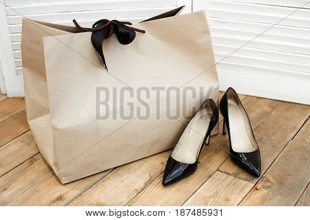 Black shoes on wooden floor with paper bag near.