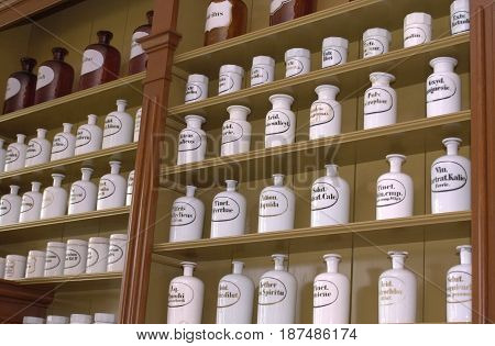 A cabinet filled iwth white pots and jars all with their individual indication of what's supposed to be in it.