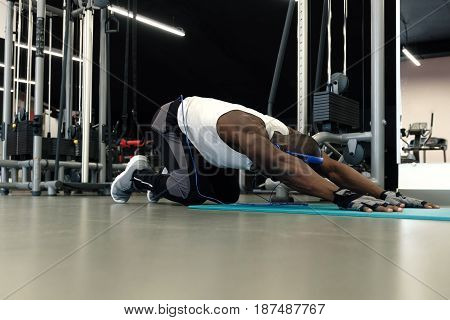 Stretching after great work out. Young handsome black man in sportswear doing stretching at gym