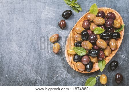 bowl with different kind of pickled olives green, black, kalamata olives over chalk board background, top view