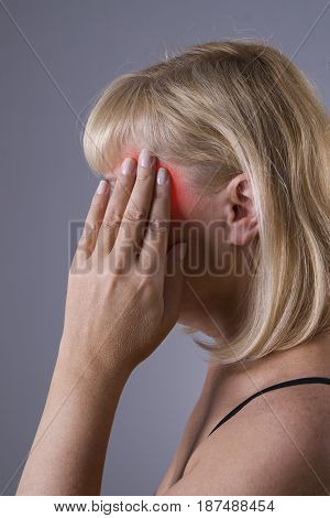 Aged blonde woman with headache migraine and depression closeup on gray background