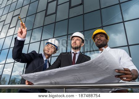 Multiethnic Group Of Professional Architects In Helmets Working With Blueprint Outside Modern Buildi