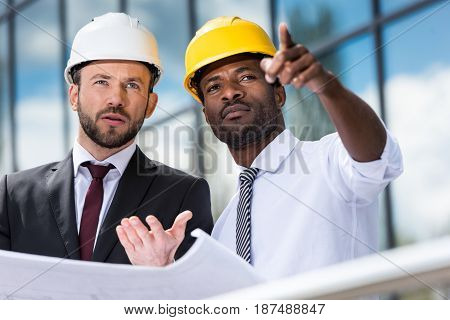 Professional Architects In Hardhats Working With Blueprint Outside Modern Building