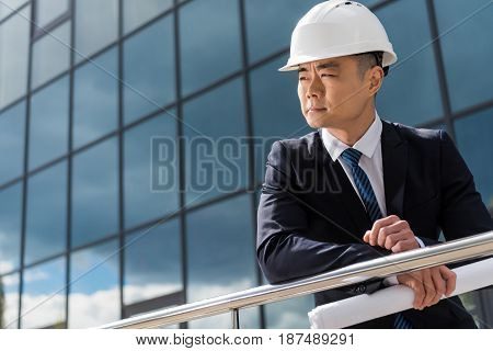 Portrait Of Professional Architect In Hard Hat Holding Blueprint