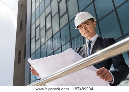 Portrait Of Serious Professional Architect In Hard Hat Looking At Blueprint