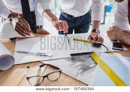 Partial View Of Team Of Architects Working On Plan Together In Modern Office