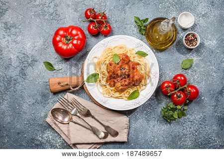Spaghetti pasta with meatballs and tomato sauce on white plate over gray background, top view