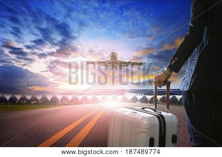 traveling man and luggage back and air plane over airport runway