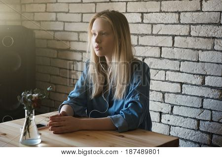 Blond girl in a blue shirt is sitting with headphones and looking thoughtfully into the distance, putting her hands together in front of her