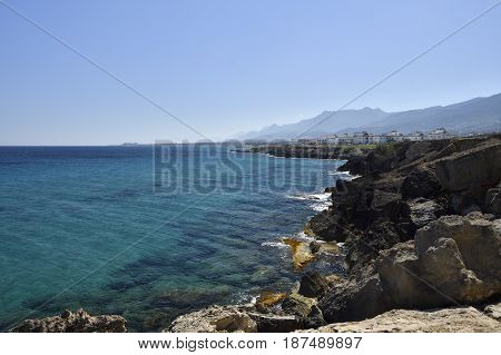 Eroded volcano stone at the beach and clear blue water and blue sky with Lapta village in the North of Cyprus in background.