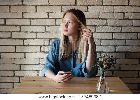 Blond girl in blue shirt sits at table holding telophone in hand and pensively looks to the side, holding the other hand with a lock of hair on the background of a light brick wall