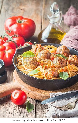Spaghetti pasta with meatballs and tomato sauce in cast iron pan over wooden background, close up