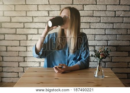 Young blonde in blue shirt sits at the table in a cafe on which lies a phone on a brick wall background. A girl drinks coffee from a black paper cup and looks to the left