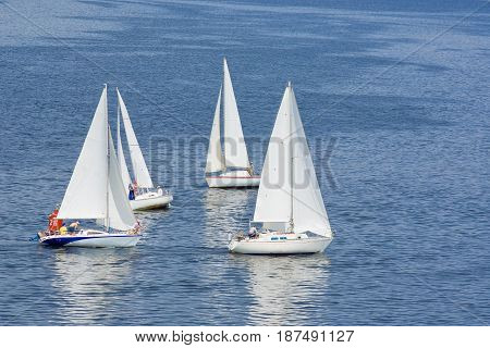Four yachts making a close turn near buoy on a summer river.