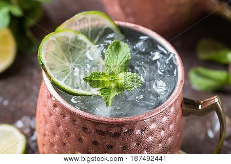 Moscow mule cocktail in copper cup with lime, ginger beer, vodka and mint garnish
