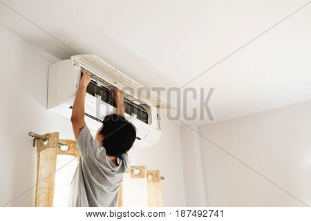 a guy cleaning air conditioning by himself, in bedroom