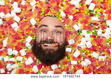 Young bearded man all covered with candies looking at camera with sweet in mouth.