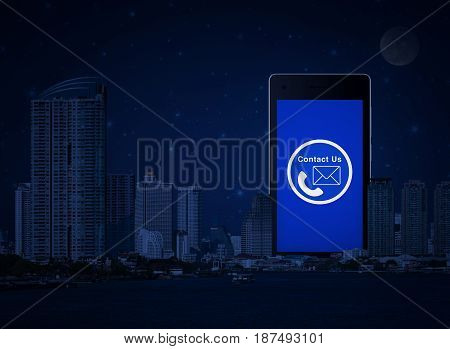 Telephone and mail icon on modern smart phone screen with office city tower river and fantasy night sky Contact us concept