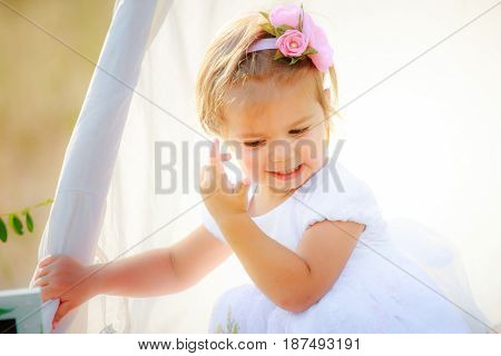 Little girl adjusts her hair and clings to edge of hut for games. Child with beautiful hairstyle in white dress.