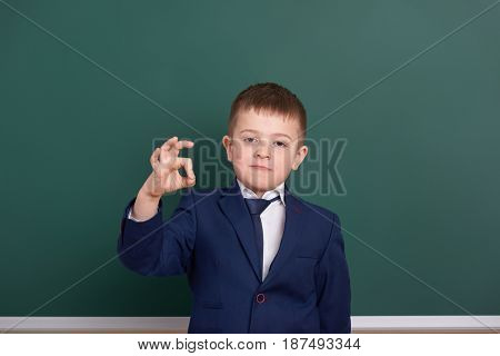 school boy show ok sign, portrait near green blank chalkboard background, dressed in classic black suit, one pupil, education concept