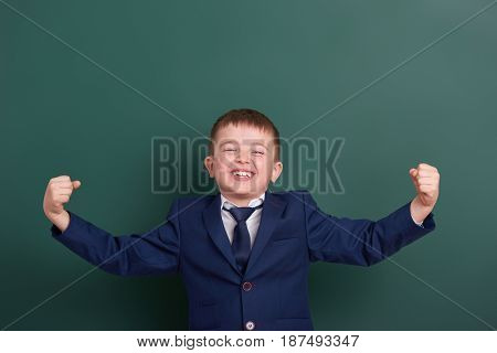 school boy show biceps muscles, portrait near green blank chalkboard background, dressed in classic black suit, one pupil, education concept