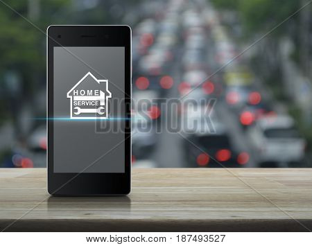 Hammer and wrench with house icon on modern smart phone screen on wooden table over blur of rush hour with cars and road Home service concept