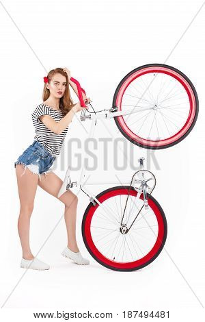 Side view of trendy model holding bicycle with wheel up and looking at camera on white background.