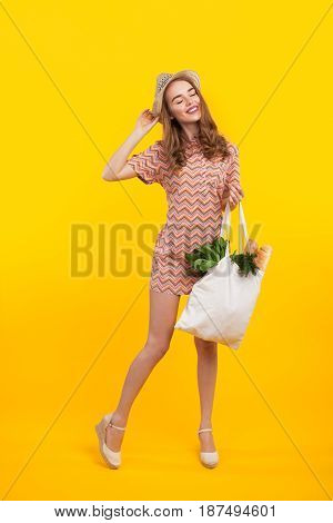 Content woman in straw hat posing on yellow background with bag full of products.