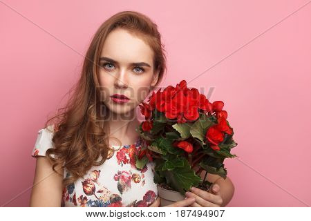 Young woman in charming dress holding flower pot and looking at camera on pink background.
