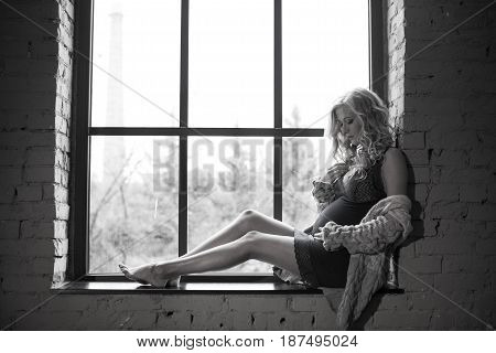 Beautiful red-haired pregnant girl is sitting on the window