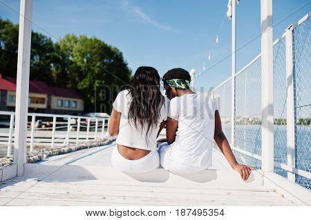 Back Of Two Stylish And Trendy African American Girls, Wear On White Clothes Against Lake On Pier Be