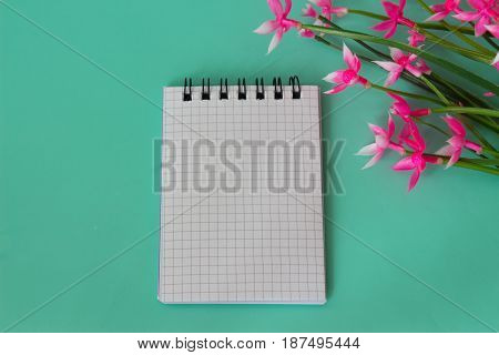 Pink flowers made of artificial materia. bouquet de fleurs and notebook on a neutral green background.
