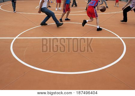 Group of teenagers playing basketball at the street playground