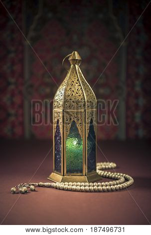 Ramadan lamp with islamic rosary beads. Islamic festive background. Traditional Egyptian ornate Ramadan lamp.