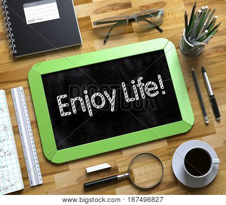 Small Chalkboard with Enjoy Life Concept. Enjoy Life Handwritten on Green Chalkboard. Top View Composition with Small Chalkboard on Working Table with Office Supplies Around. 3d Rendering.