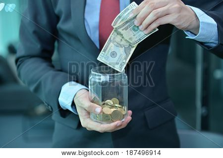 Businessman Holding And Saving Money Banknotes In A Wooden Jar