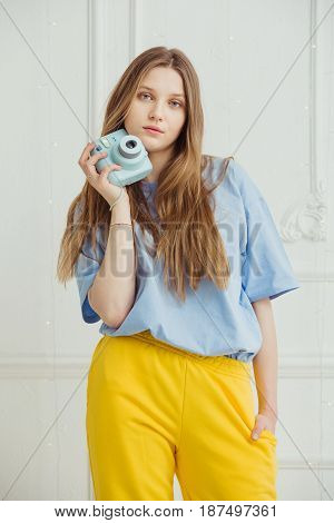 Girl in casual cloth stands with video camera in hand. Young woman with long hair dressed in cosy home clothes posing with camera in blue t-shirt and yellow trousers