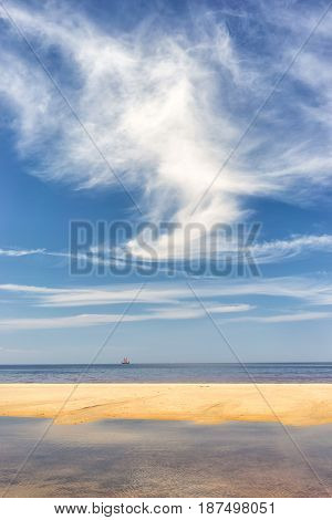 Vintage sailboat on the horizon of the Baltic sea on the background of beautiful clouds and thin strips of yellow sandy beach
