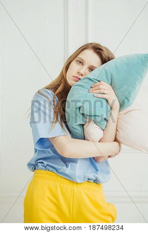 Tired woman holds pillow in hands. Girl without make up wants to fall asleep. Sleepy lady with long luxury hair in the morning or at night going to sleep. Drowsy female hugging big bolster