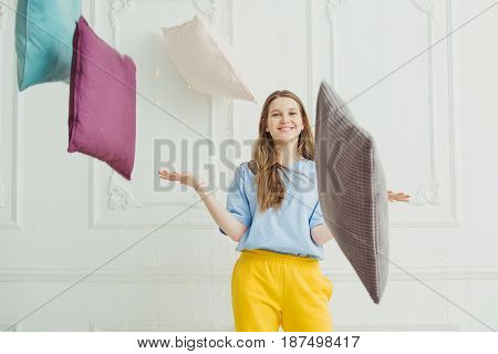 Smiling girl throwing pillows in front of the wall. Happy playful woman in pyjama and flying bolsters, cheerful lady play with pillow. Teenager in a pillow-fight