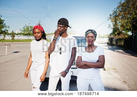Three Stylish African American Friends, Wear On White Clothes Against Two Luxury Cars. Street Fashio